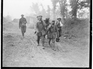 German Prisoners Wearing Gas Masks Bring in Wounded, Amiens, August 1918