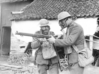Two Soldiers Wearing Gas Masks Examining a Lee Enfield Rifle, France, March 1917.