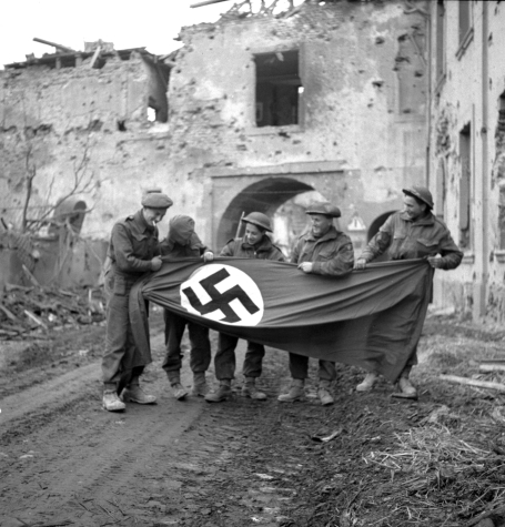 This photo was taken on March 9, 1945. It shows five Canadian soldiers, smiling and displaying a German flag bearing the Nazi swastika, which they've taken from a fortified house riddled with bullet holes in the town of Xanten, Germany.
