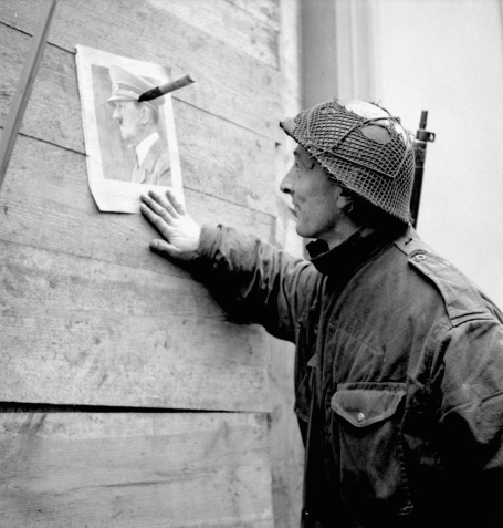 In this photo, taken February 28, 1945, a soldier of the 2nd Canadian Infantry Division is seen in profile looking at a portrait of Adolf Hitler fixed with a knife to the wall of a house in Calcar, Germany.