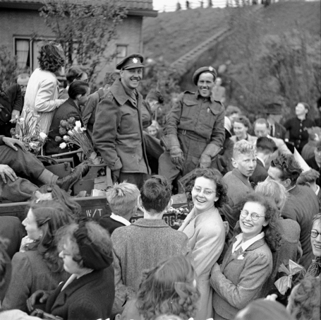 In this photo taken on May 9, 1945, two Canadian soldiers in uniform perched on a Universal Carrier bound for Rotterdam are surrounded by Dutch civilians joyfully celebrating the liberation of the Netherlands.