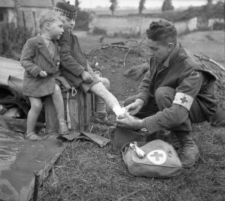 The photo shows a member of the army Medical Corps kneeling in front of a boy and bandaging his right leg, while the boy's younger brother looks on. It was taken in Normandy, France, June 19, 1944.