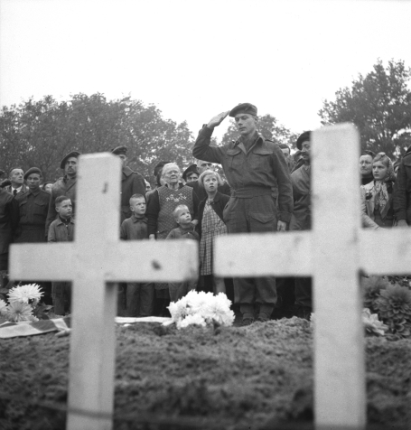 Photo d'un major en uniforme faisant le salut militaire devant la tombe d'un soldat, alors qu'on aperçoit à l'avant-plan deux grandes croix blanches, à Ossendrecht (Pays-Bas), le 26 octobre 1944.