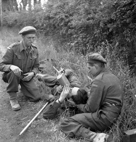 In the photo, a Canadian Sergeant with a broken leg lies in the grass, drinking from a canteen, while two other soldiers help him. Bayeux, France, June 14, 1944.