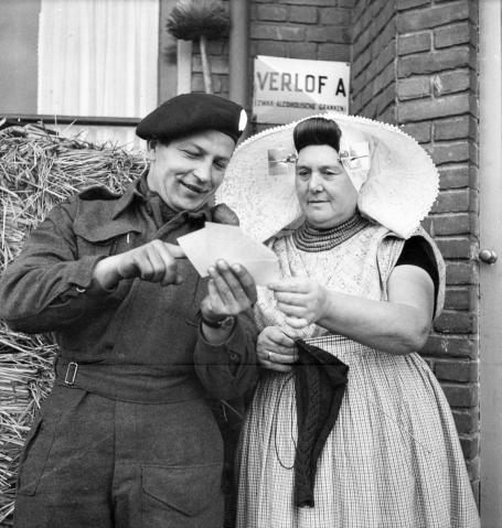 Photo of a soldier in uniform showing snapshots from home to a woman in traditional Dutch costume. It was taken in Goes, in the Netherlands, November 1, 1944.