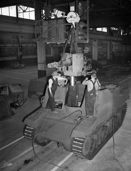Photo showing four male workers and one female assembling a Sexton self-propelled gun at the Montreal Locomotive Works, Quebec,  August 1944.