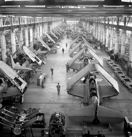 The photo shows an overview of the shop floor of an aircraft factory, with employees working around the planes on an assembly line in Fort William, Ontario, circa 1944.