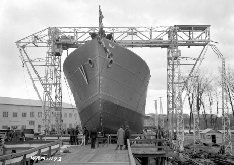 The photo shows the corvette HMCS La Malbaie under the scaffolding of a mobile crane just before being inaugurated at the shipyard of Marine Industries Ltd., Sorel, Quebec, October 25, 1941.