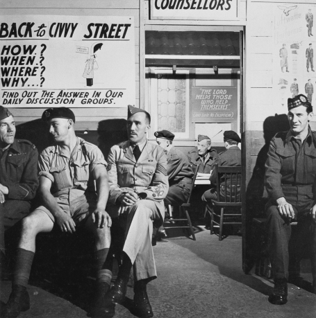This photo shows four men in military uniform waiting their turn outside a demobilization office, Toronto, Ontario, in 1944.