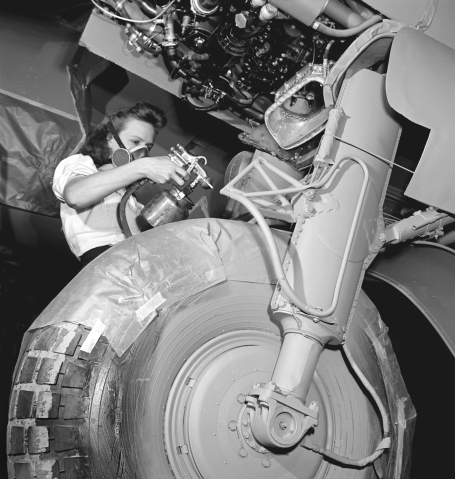 This photo shows a female worker, wearing a mask, and spray painting the landing gear of a De Havilland Mosquito airplane on the assembly line of a factory in Downsview, Ontario, September 1944.