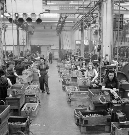 The photo shows two rows of seated women making cartridges at the Dominion Arsenal factory in Saint-Malo, Quebec, in April 1942.