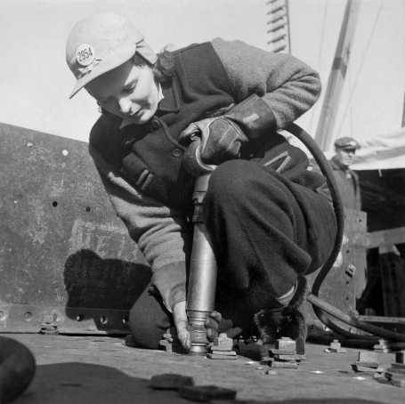 Photo of worker Mrs. A. Mackay kneeling to use a riveting gun at Pictou Shipyards Ltd, Nova Scotia, January 1943.