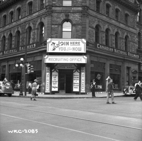Photo of a Canadian Army Recruiting Office. Pedestrians walk past the building, the front of which is covered in messages exhorting potential volunteers to join up. Ottawa, Ontario, August 1941.