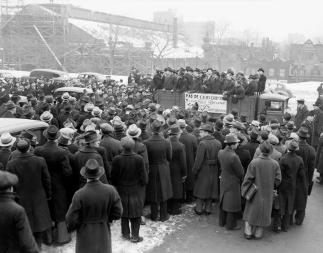 A photo showing a crowd of men at an anti-conscription rally organized by Montreal students. Men are packed into the back of an open truck and the crowd stands close by. Montreal, Quebec, March 23, 1939.