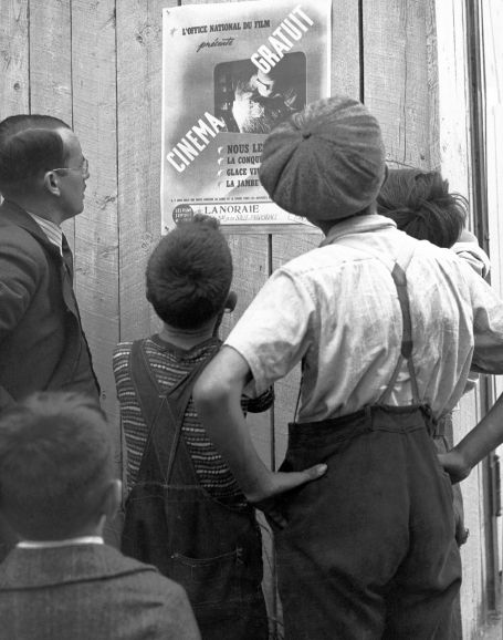 This photo shows a group of five citizens in front of a French poster announcing the free screening of NFB films in Lanoraie, Quebec, circa 1942.