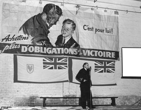 In this photo, an officer of the Royal Canadian Navy Volunteer Reserve speaks to factory workers at the Canadian International Paper mill in Gatineau, Quebec, before a screening of NFB films for the industrial circuit, May 1945.