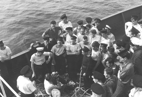 A film still from Corvette Port Arthur, showing a cameraman filming a group of sailors on the deck of the corvette.