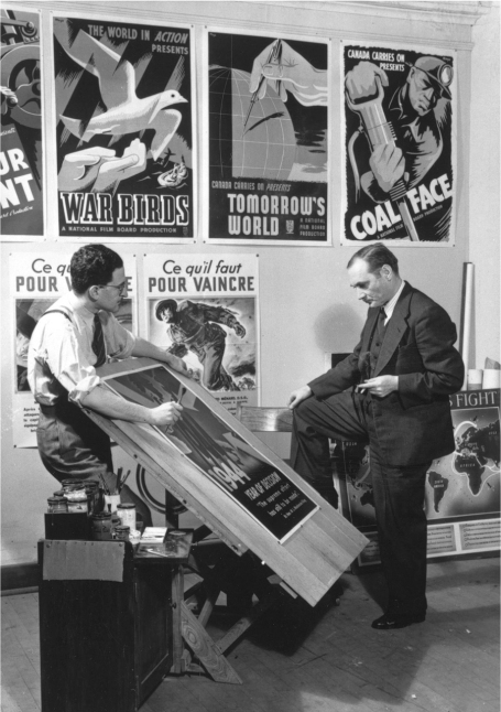 This photo shows John Grierson and Harry Mayerovitch standing in front of a wall covered in film and propaganda posters, discussing the design of a new poster lying on a drafting table.