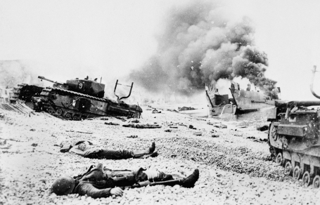 Photo showing the beach at Dieppe on August 19, 1942, after Operation Jubilee. The bodies of dead Canadian soldiers lie not far from abandoned tanks and landing craft giving off thick smoke.