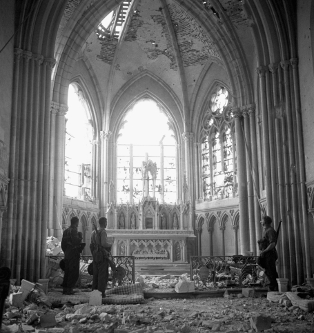 Photo of the interior of a ravaged church in Carpiquet, France, July 12, 1944. Immobile amid the ruins, three Canadian soldiers of the 9th Infantry Brigade look at the altar and broken windows through which the light pours in.