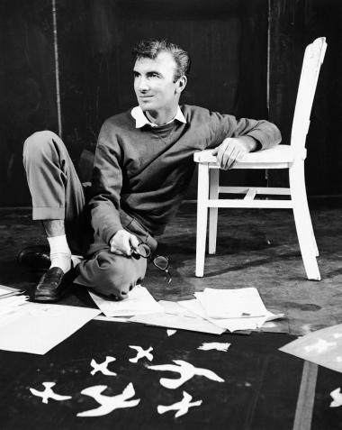 Norman McLaren during a photo session with some of his ongoing projects spread out around him.